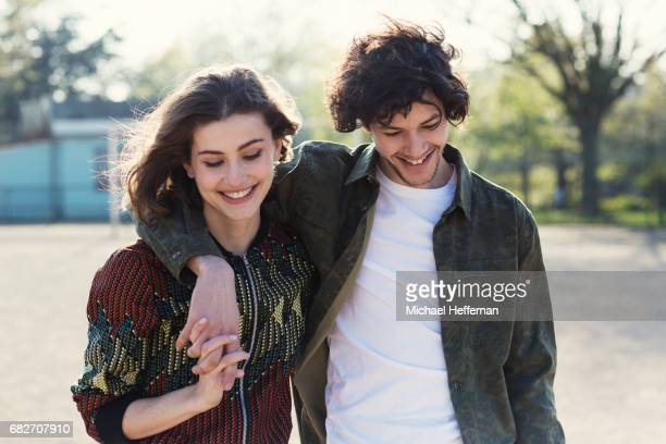 young couple smiling and walking in park - adults only stock pictures, royalty-free photos & images