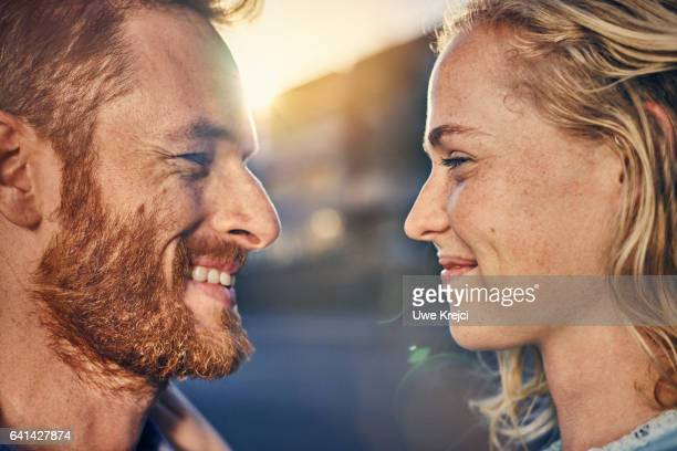 young couple smiling at each other, close up - angesicht zu angesicht stock-fotos und bilder