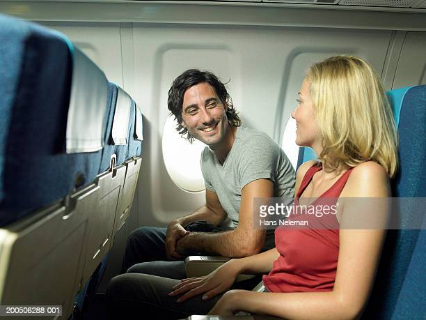 Young couple smiling at each other in airplane