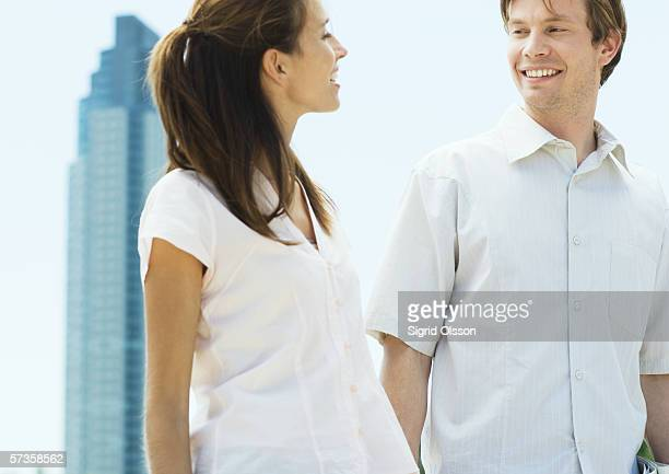 Young couple smiling at each other in urban setting