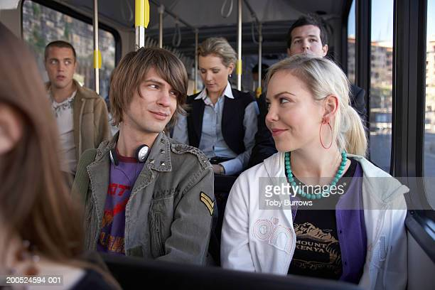 Young couple smiling at each other on bus
