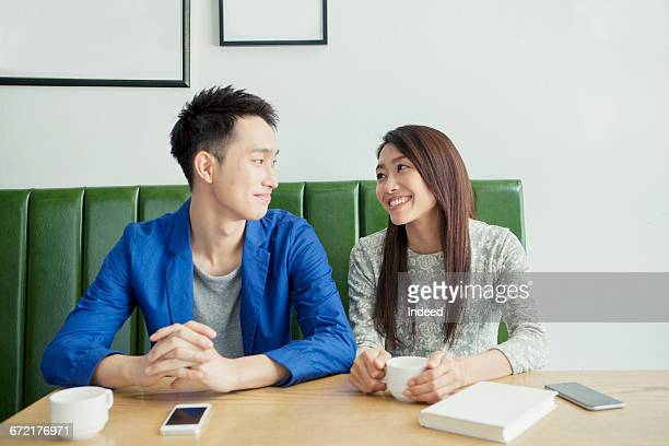 Young couple smiling face to face at café