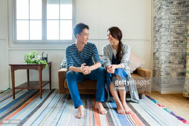 Young couple smiling face to face on sofa
