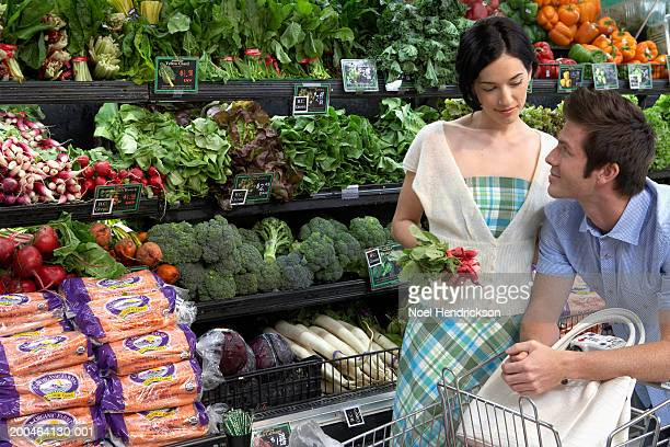 Young couple smiling in produce aisle, side view, close-up