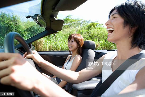 Young couple smiling in the car, man holding steering wheel, Saipan