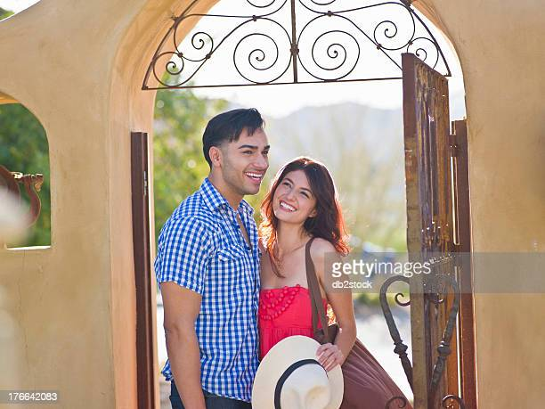 Young couple smiling together at entrance to villa