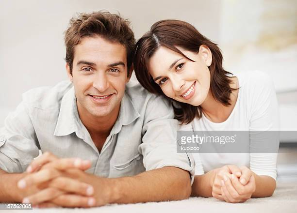 Young couple smiling together while lying on floor
