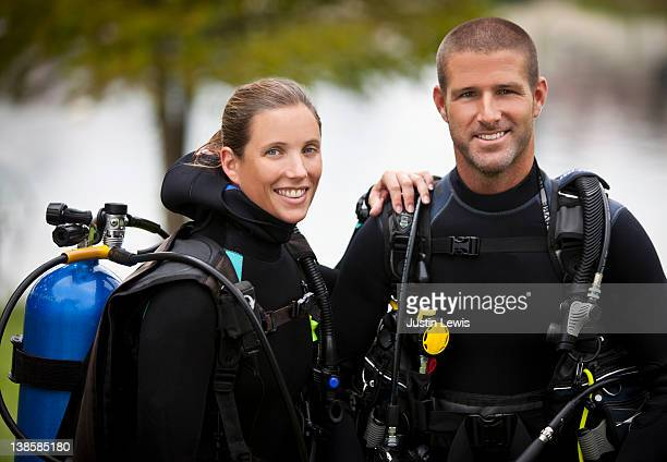 Young couple smiling wearing diving gear