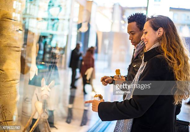 Young couple snacking and looking at shop window display, Milan