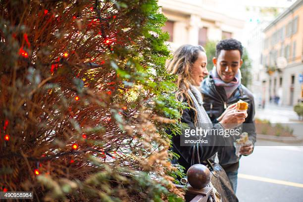 Young couple snacking outdoors, Milan