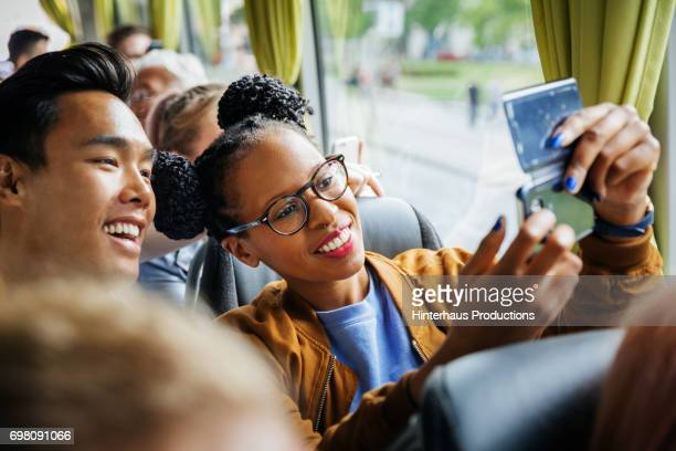 Young Couple Snapping Selfie Together During A Bus Journey