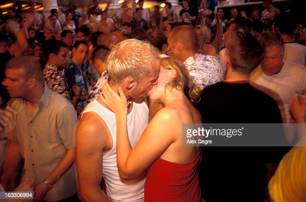 Young couple snogging in a crowded nightclub