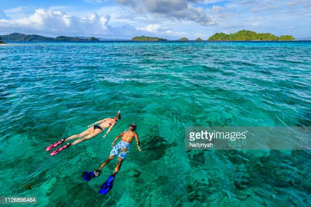 young couple snorkeling on east china sea, philippines - palawan stock pictures, royalty-free photos & images