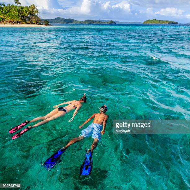 young couple snorkeling on east china sea, philippines - el nido stock pictures, royalty-free photos & images