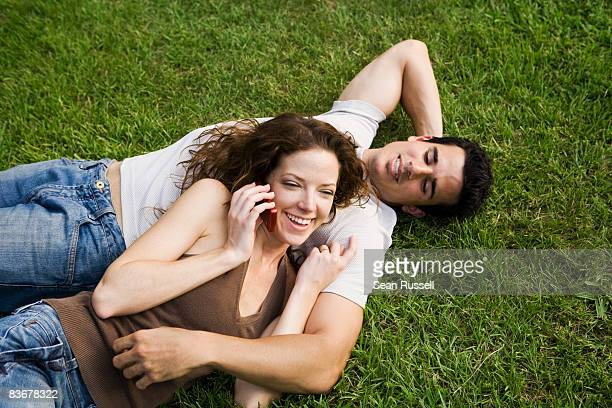 a young couple snuggling on a lawn - cary stockfoto's en -beelden