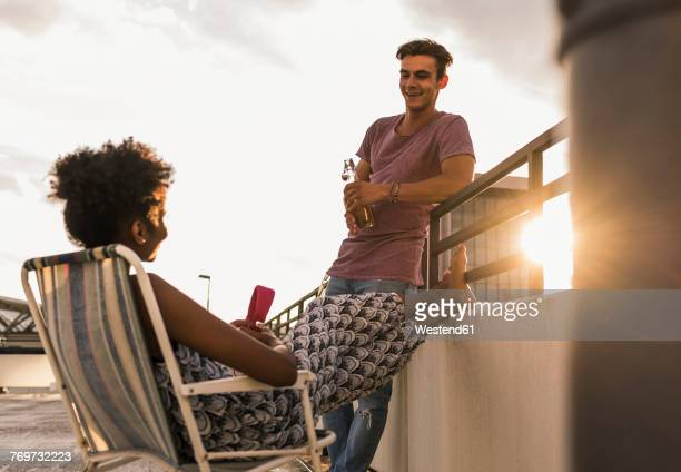 Young couple socializing on rooftop
