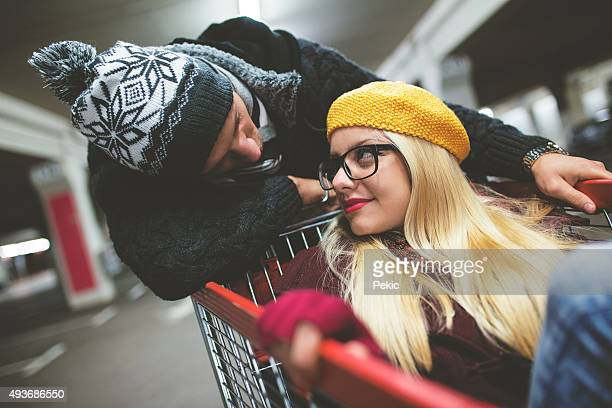 Young Couple Speed Shopping At Christmas Time