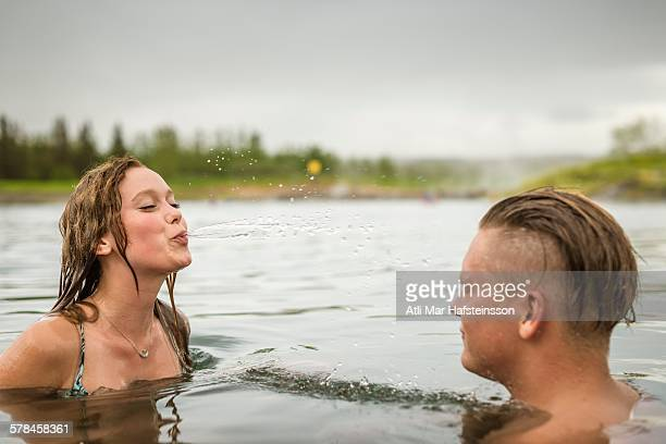 Young couple squirting water in Secret Lagoon hot spring (Gamla Laugin), Fludir, Iceland