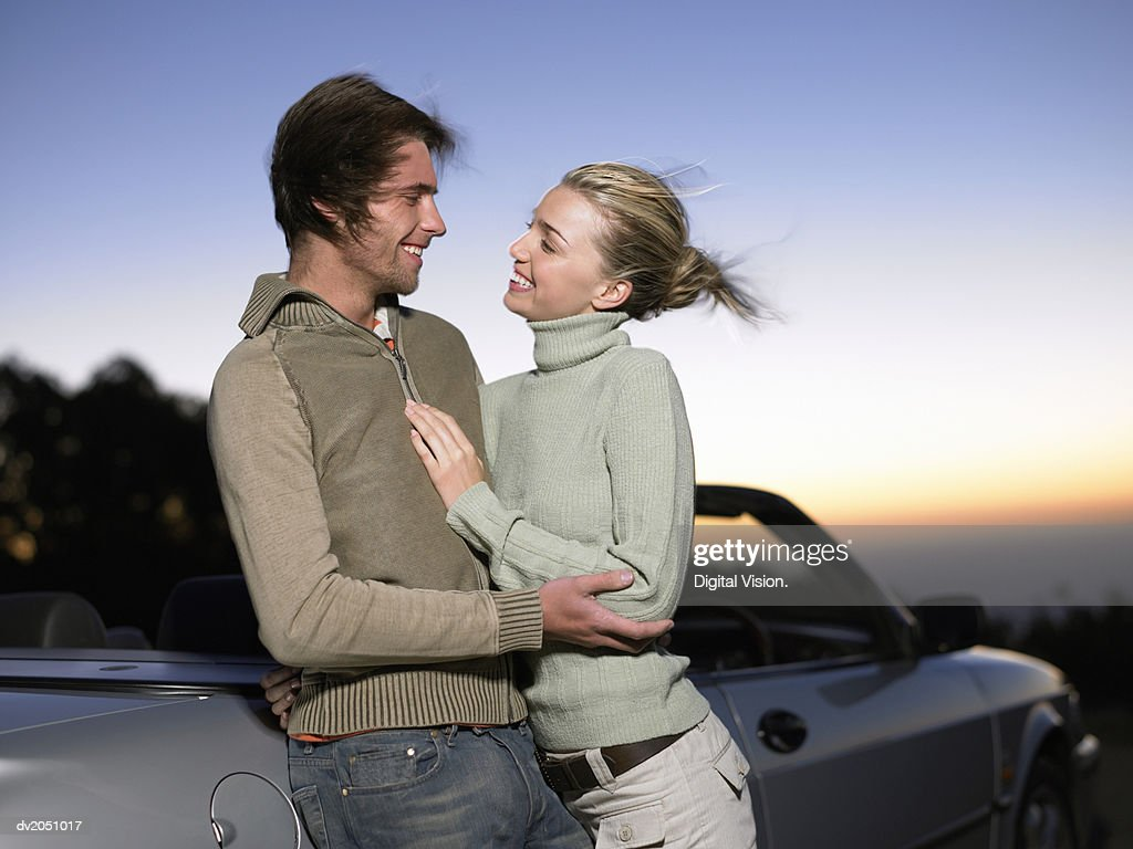Young Couple Stand by a Parked Convertible Car at Twilight, Embracing : Stock Photo