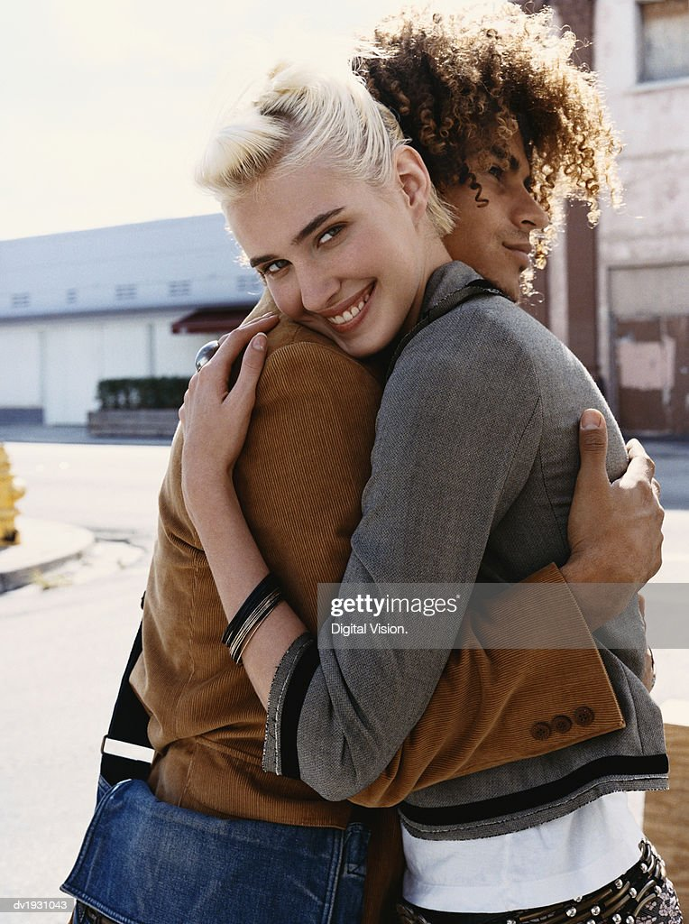 Young Couple Stand in an Urban Setting, Embracing : Stock Photo