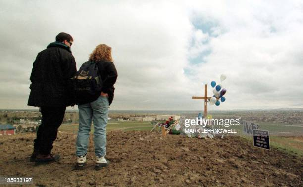 A young couple stand in silence while paying their respects during a memorial service held 25 April 1999 in Clement Park for the students who were...