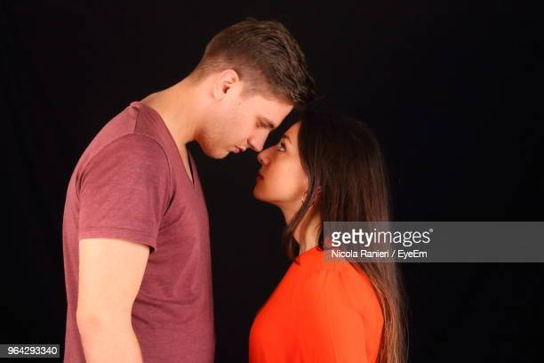 Young Couple Standing Against Black Background