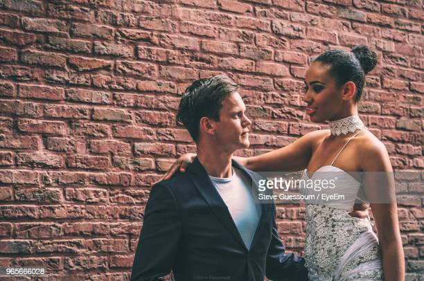 Young Couple Standing Against Brick Wall