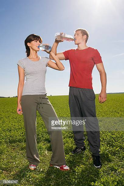Young couple standing and drinking from water bottle