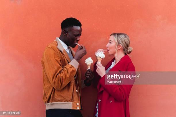 young couple standing at an orange wall eating ice cream - eis essen stock-fotos und bilder