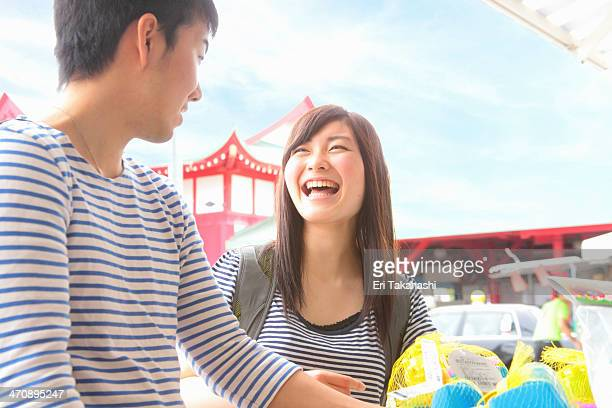Young couple standing at market stall laughing