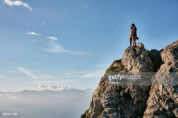 Young couple standing at top of mountain, looking at view, Innsbruck, Tyrol, Austria