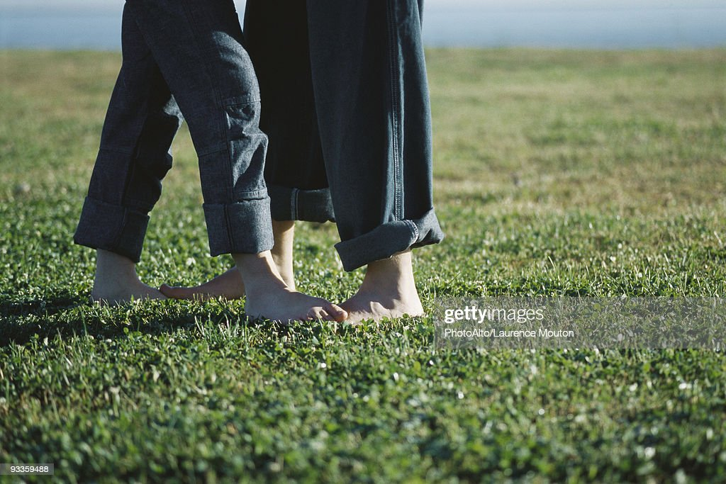 Young couple standing barefoot in field, low section : Stock Photo
