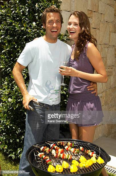 Young couple standing by bbq, laughing, portrait