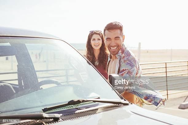 young couple standing by car, at beach, laughing - next to stock pictures, royalty-free photos & images