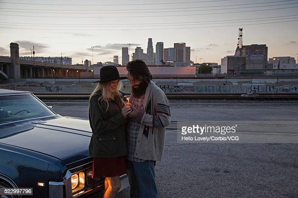 Young couple standing by car on road and holding burning candle