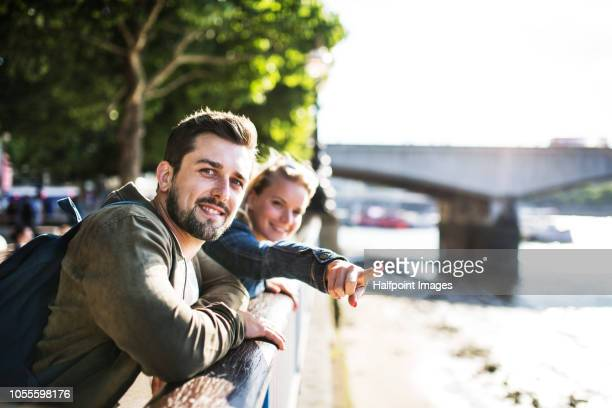 A young couple standing by the river in a city, pointing to something.