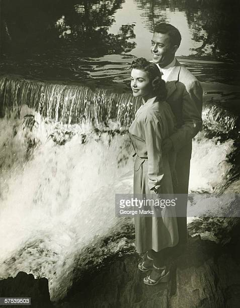 Young couple standing by waterfall, (B&W)