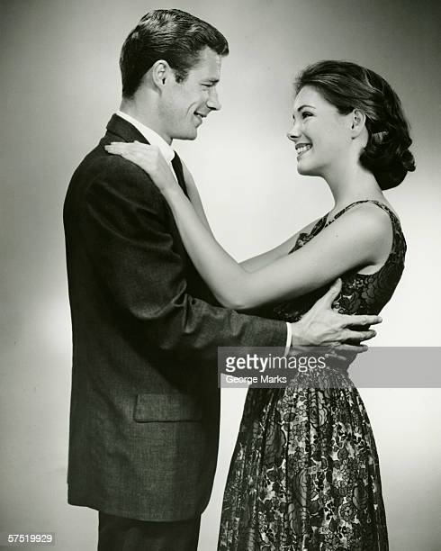Young couple standing face to face, smiling, in studio, (B&W)