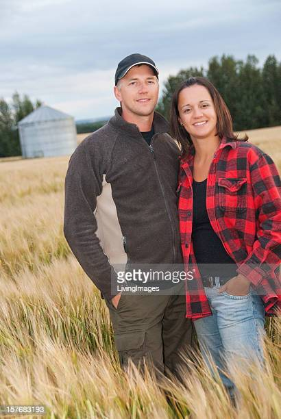 Young couple standing in a wheat field on farm