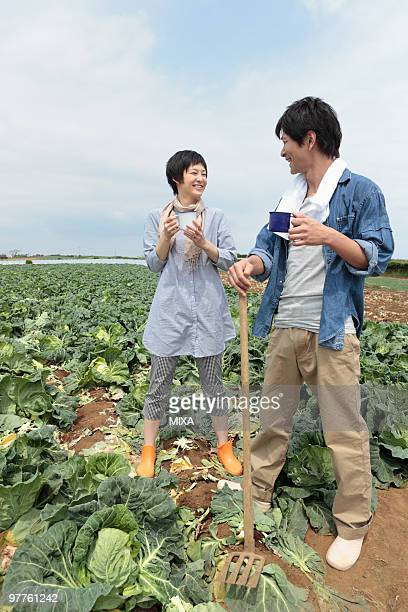 Young couple standing in cabbage field