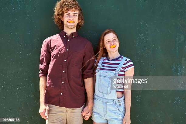 young couple standing in front of a green wall with orange slices in their mouth - freaky couples stock photos and pictures
