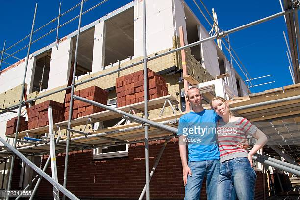 A young couple standing in front of a house construction