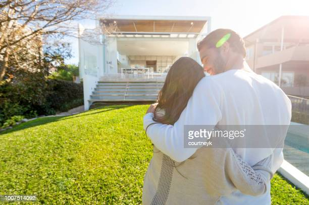 young couple standing in front of a modern new house. - house stock pictures, royalty-free photos & images