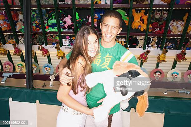 young couple standing in front of amusement park game, portrait - indie series awards stock photos and pictures