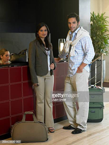 Young couple standing in hotel lobby, portrait