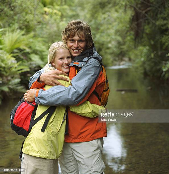 Young couple standing in stream, embracing