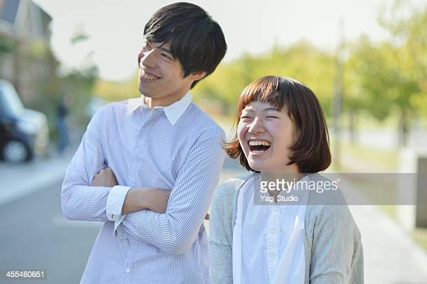 young couple standing in the residential area - 笑う ストックフォトと画像