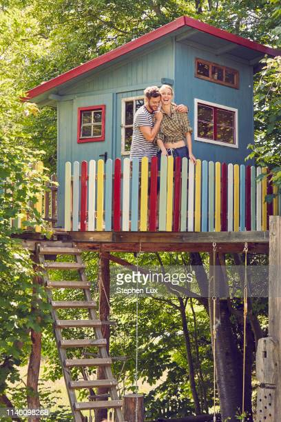 young couple standing in tree house, hugging, laughing - tree house stock pictures, royalty-free photos & images