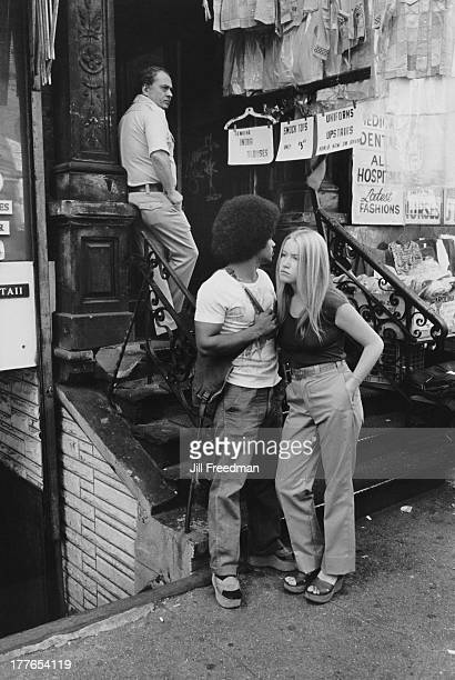 A young couple standing next to a shop in the Lower East Side New York City circa 1975