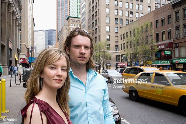 a young couple standing on a city street, new york city - staring stock photos and pictures